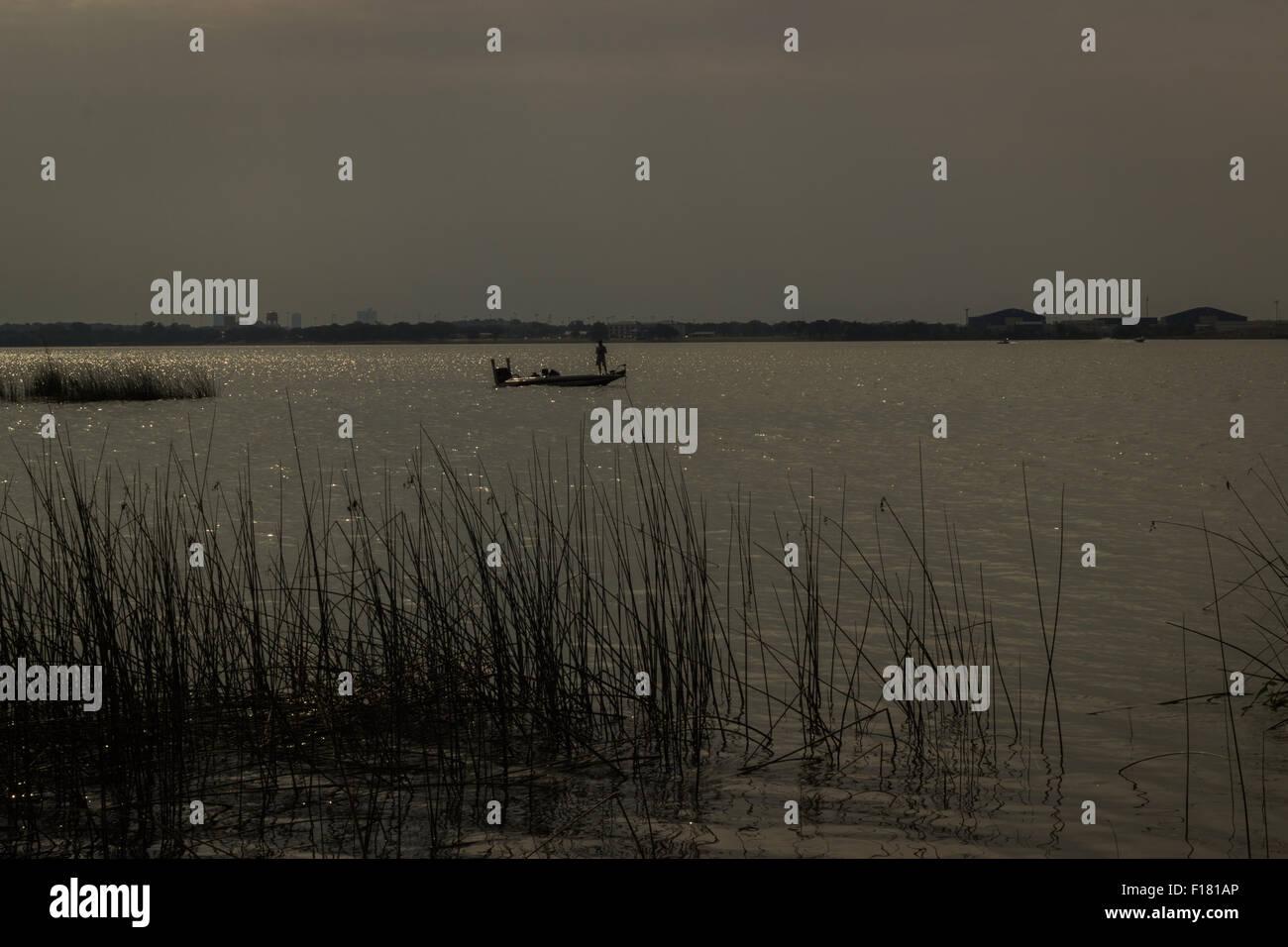 Silhouette Mann auf Boot am See Stockfoto