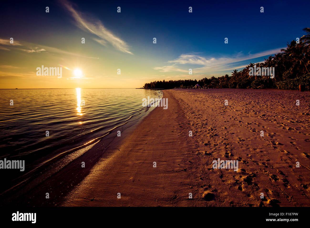 Fußabdrücke am tropischen Strand bei Sonnenuntergang mit Sonne über dem Ozean Stockbild