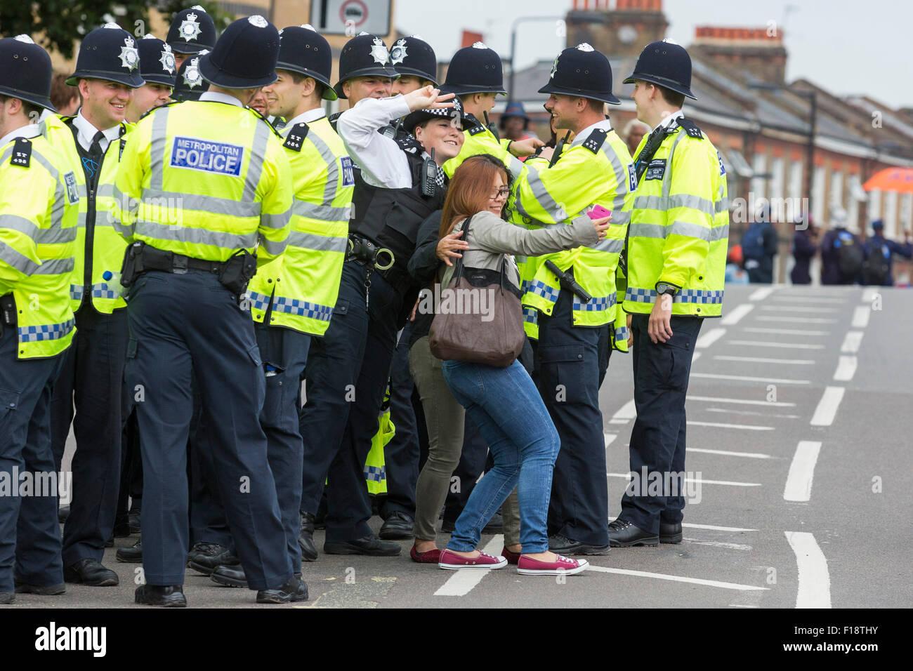 London, UK. 30. August 2015. Eine Polizistin posiert für ein Selbstporträt mit Feiernden. Der Notting Stockbild