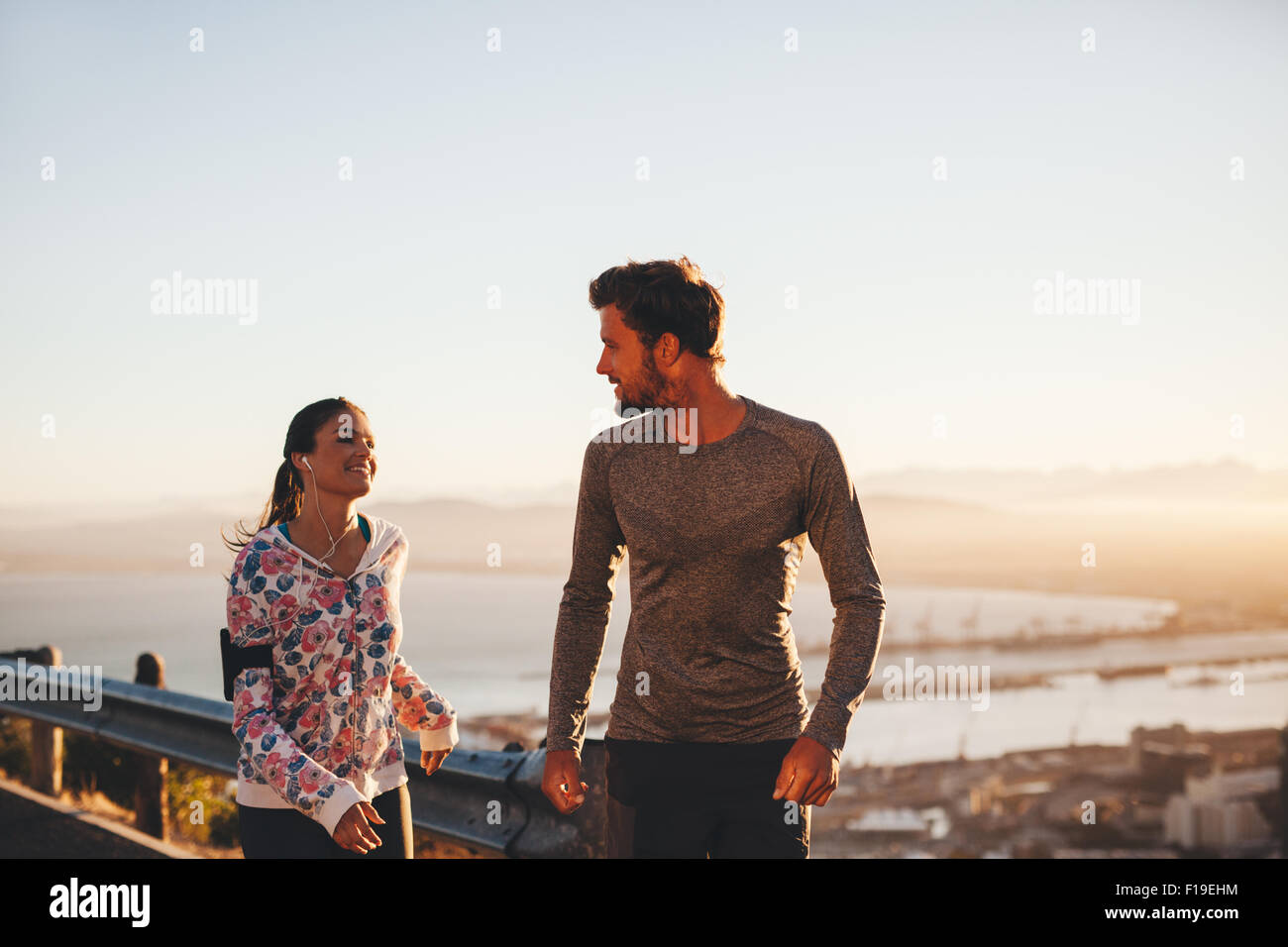 Bild des Fit junger Mann und Frau Joggen auf Landstraße, betrachten einander. Läufer genießen Morgenlauf. Stockbild
