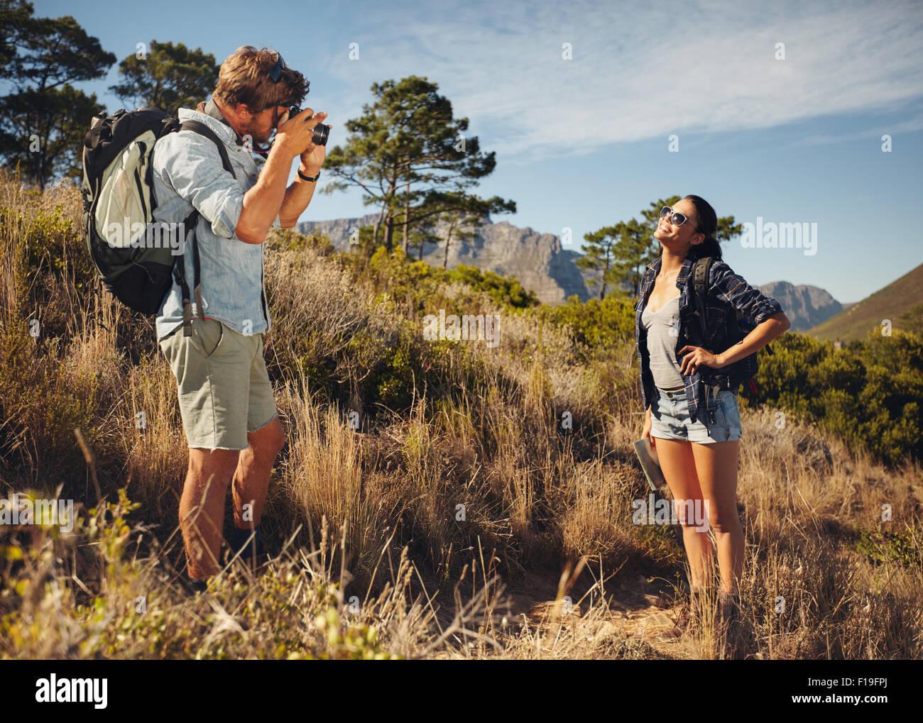 Im Freien Schuss von touristischen paar Wandern und Fotografieren mit der Kamera. Mann unter Bild der Freundin im Stockbild