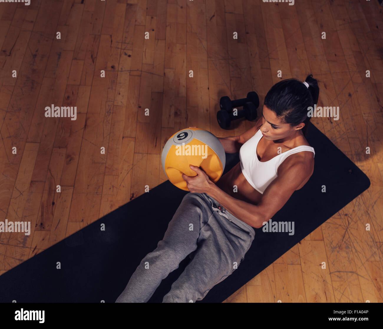Draufsicht der starke junge Frau tut Core Training mit Kettlebell Gewicht. Muskulöse Frauen auf Fitness-Matte Stockbild