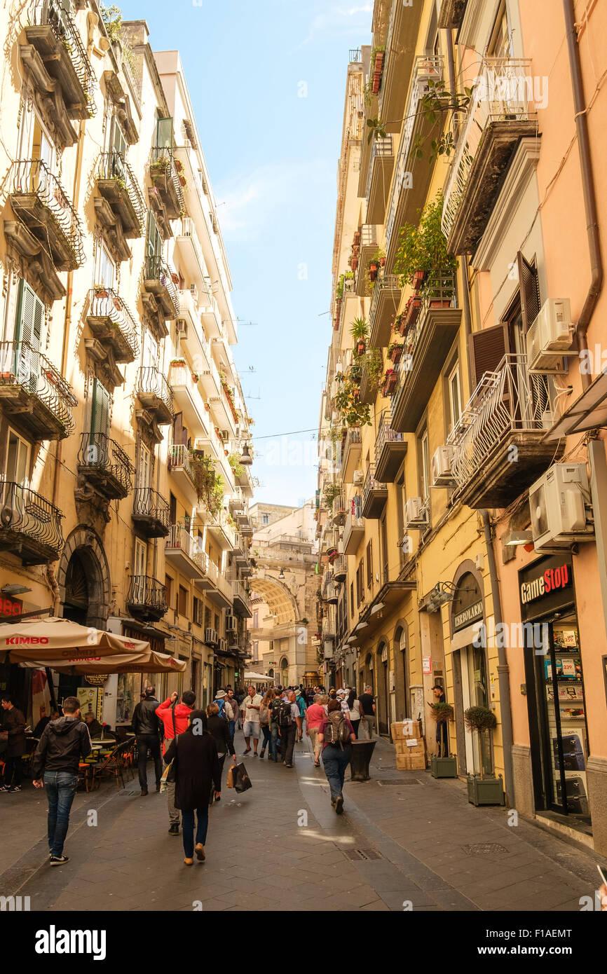 Verkehrsberuhigten Seitenstraße in Neapel, flankiert von Geschäften und Gebäuden mit Balkonen. Stockbild