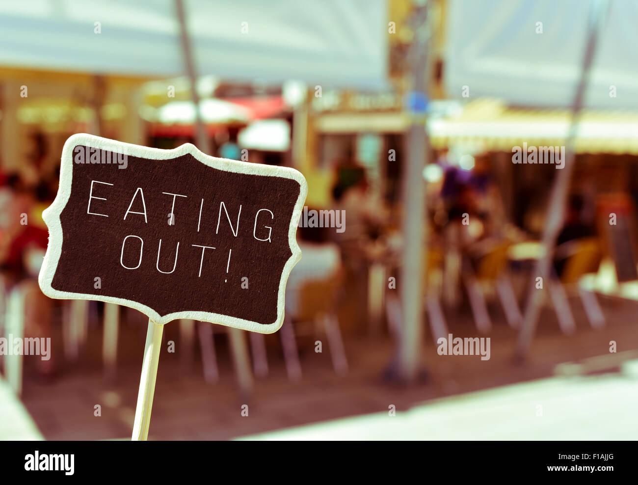 Nahaufnahme von einer Tafel mit dem Text, Essen und trinken, in der belebten Terrasse eines Restaurants Stockbild