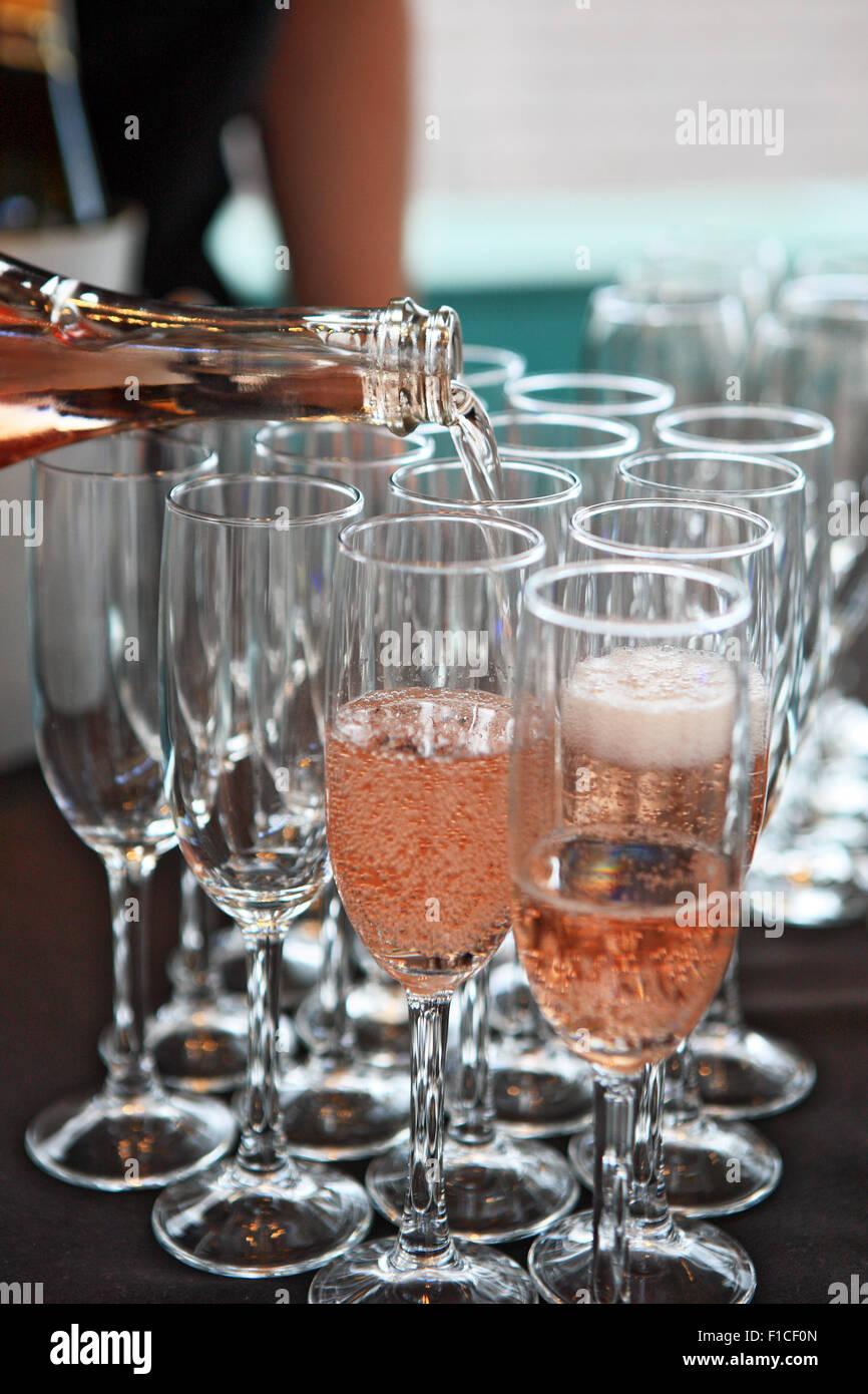 Champagner in Champagner-Gläser gegossen Stockbild