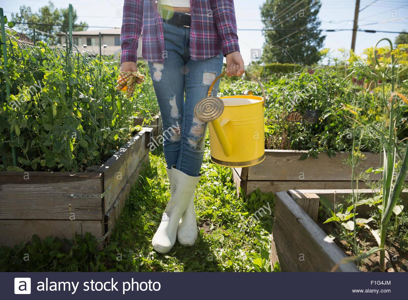 Junge Frau Gummistiefel halten Gießkanne Garten Stockbild
