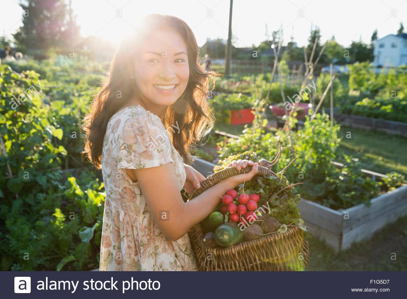 Lächelnd Teenagerin, die Ernte von Gemüse im Garten Stockbild