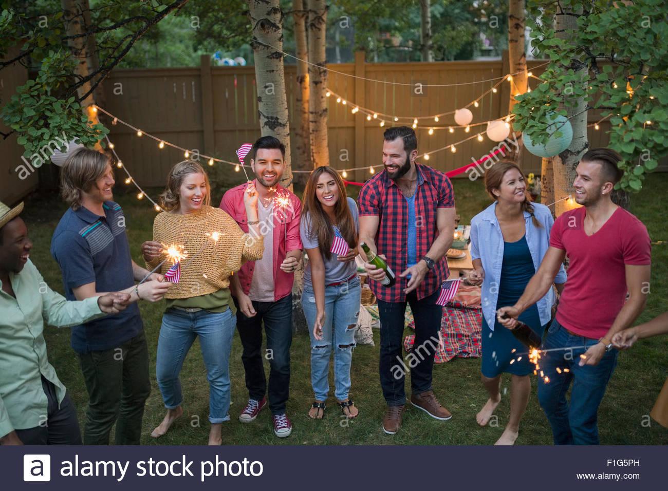 Freunde mit Wunderkerzen auf Hinterhof-party Stockbild