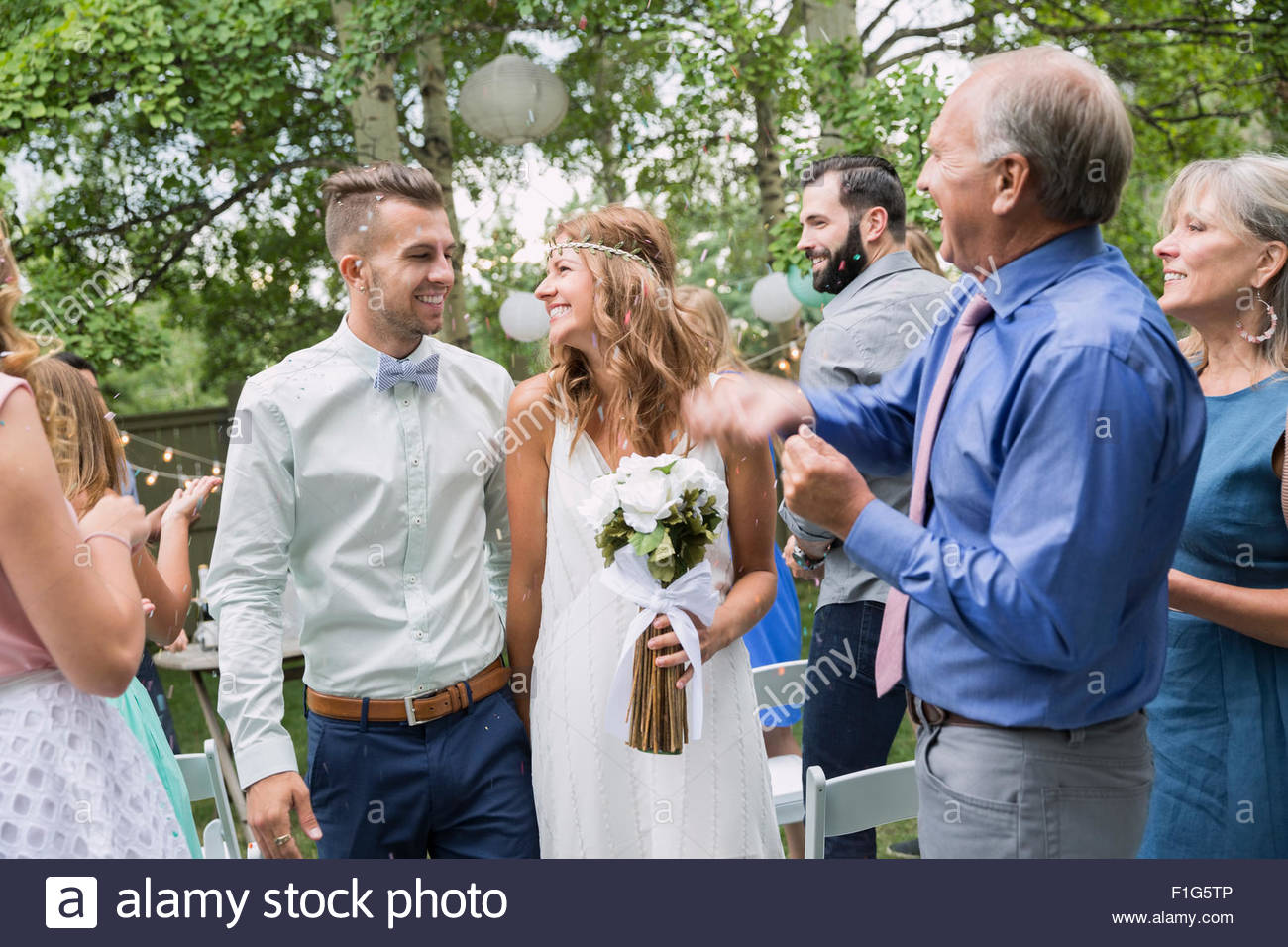 Gäste klatschten für Braut und Bräutigam Hinterhof Hochzeit Stockbild