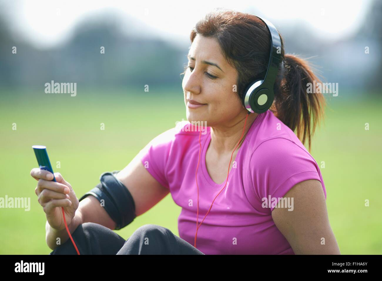 Reife Frau Übung Pause im Park Auswahl Musik vom MP3-player Stockbild