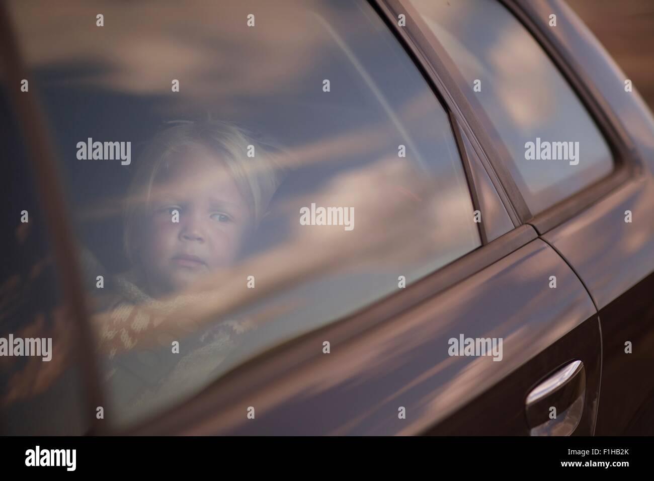 Junge auf der Suche durch Autofenster Stockbild