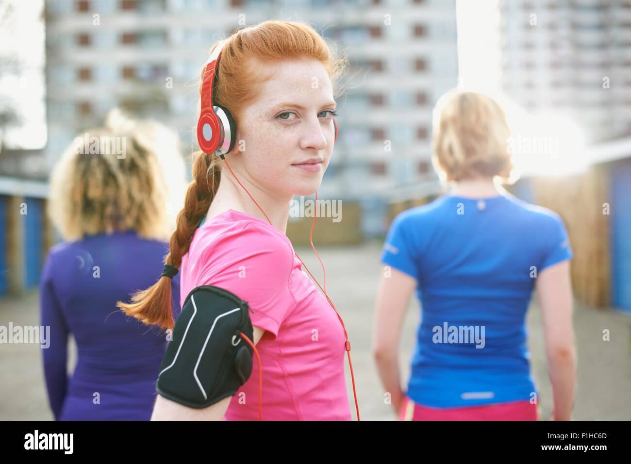 Porträt Frau mit Armbinde und Kopfhörer vor dem Training über die Schulter in die Kamera schaut Stockbild
