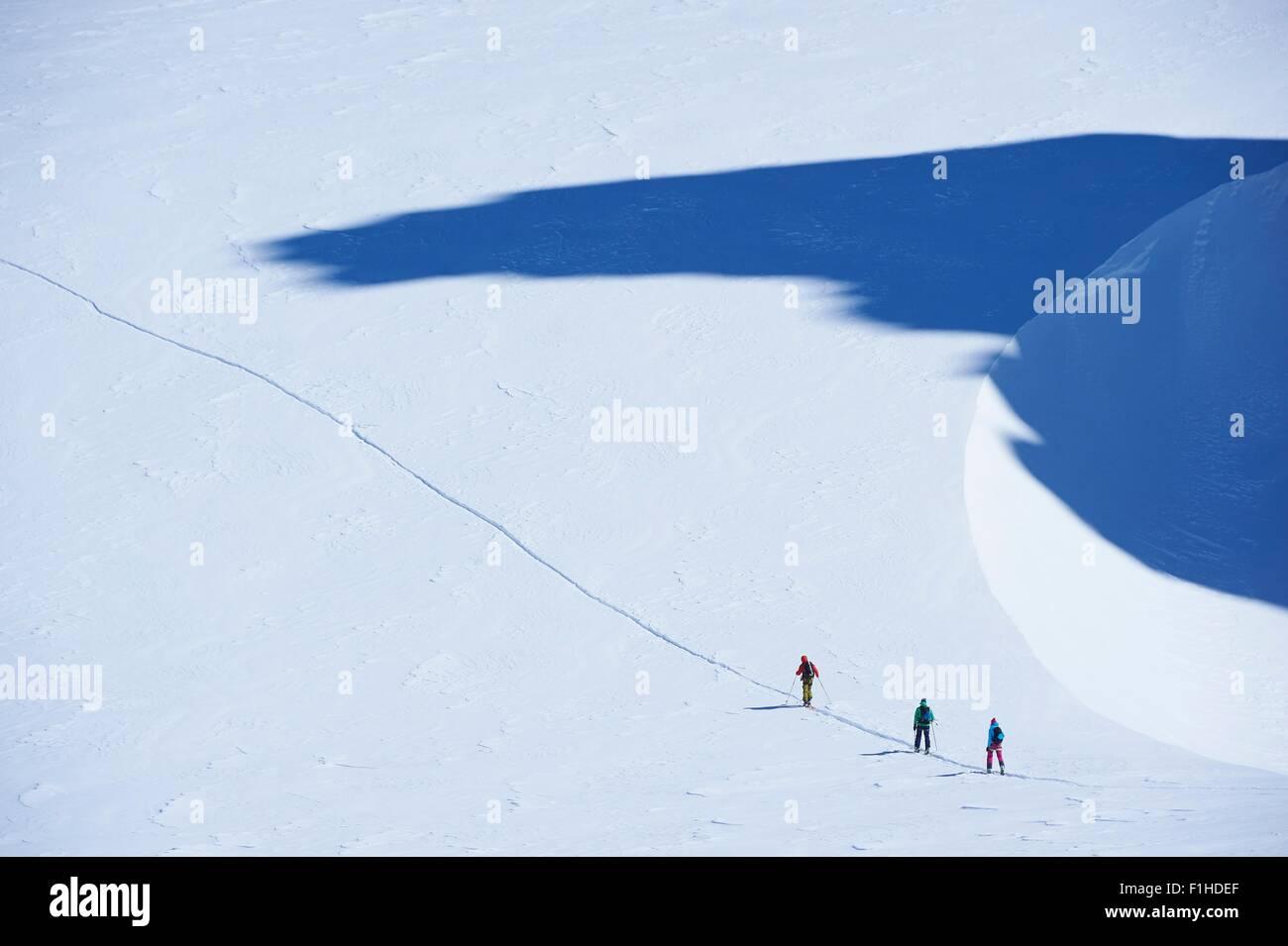 Fernblick über drei Skifahrer auf der Strecke, Mont-Blanc-Massiv, Graian Alpen, Frankreich Stockbild