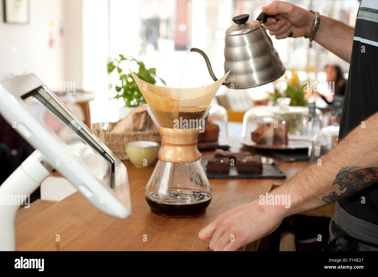 Händen des Café Kellner gießt kochendes Wasser in Topf Filterkaffee Stockbild