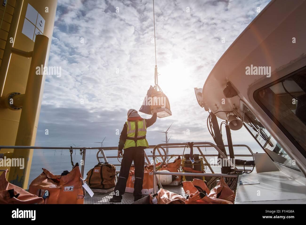 Deck Arbeiter Windenbetrieb Teile bis zu Windkraftanlagen im Offshore-Windpark Stockbild