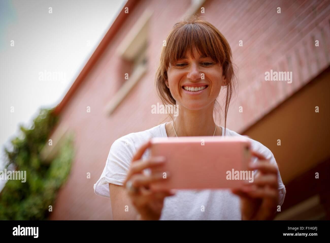 Low und Blick auf Mitte Erwachsene Frau mit Smartphone, Lächeln Stockbild