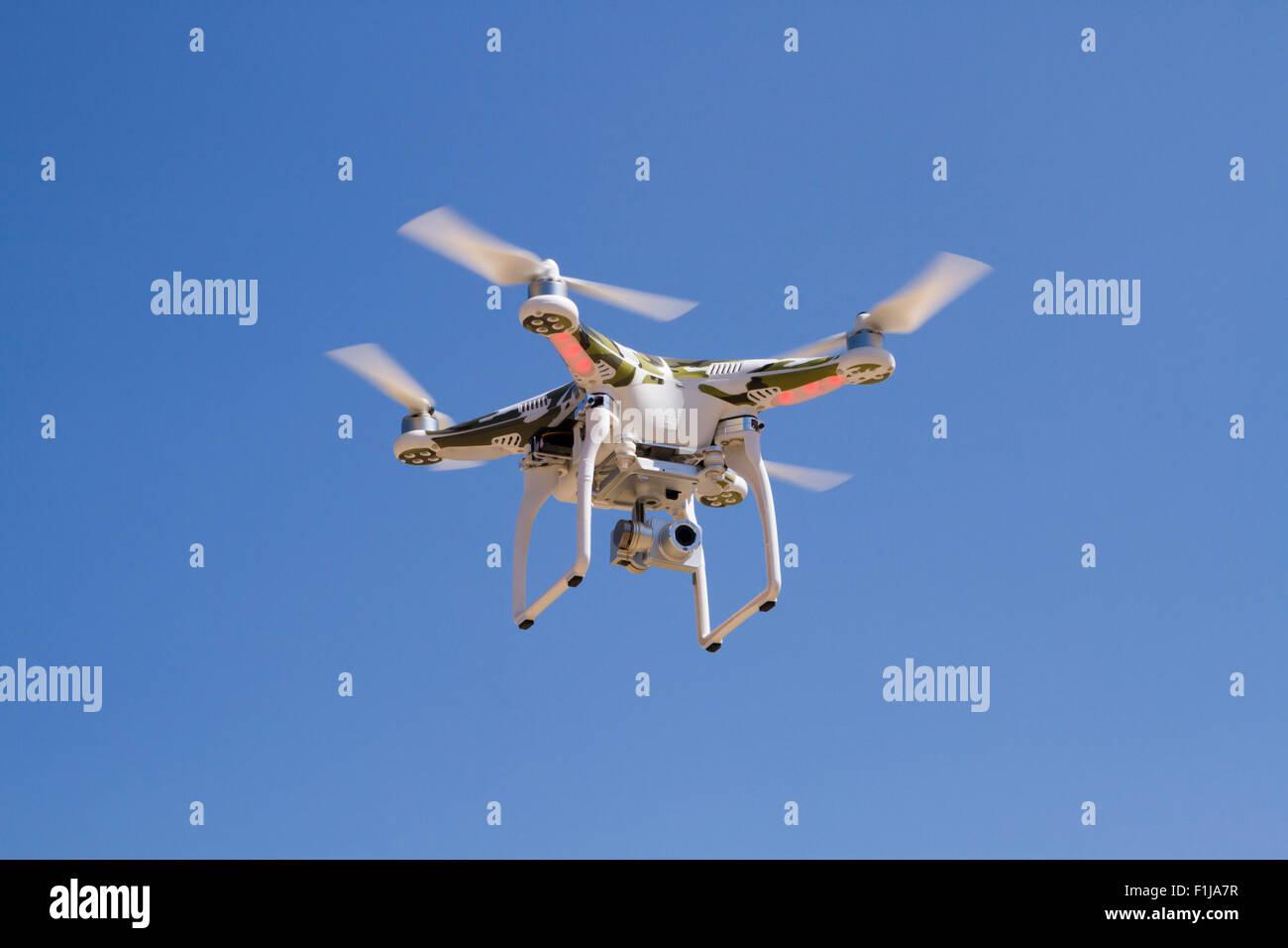 Quadrocopter mit einer Kamera vor einem blauen Himmel schweben zu tarnen Stockbild
