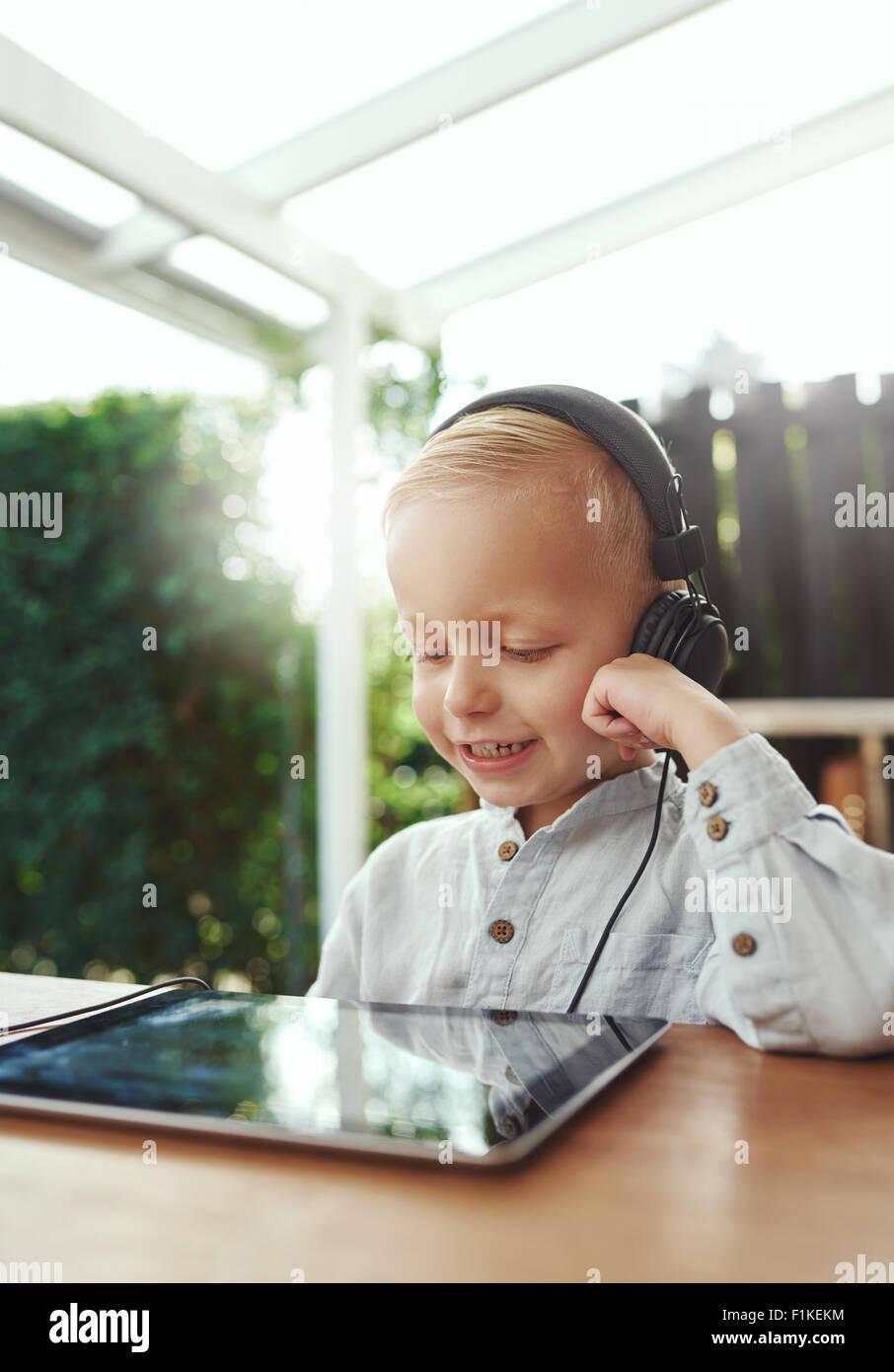 Kleiner Junge lächelnd in Freude, als er auf seinem Tablet-pc mit Stereo-Kopfhörer beim Sitzen im freien Stockbild