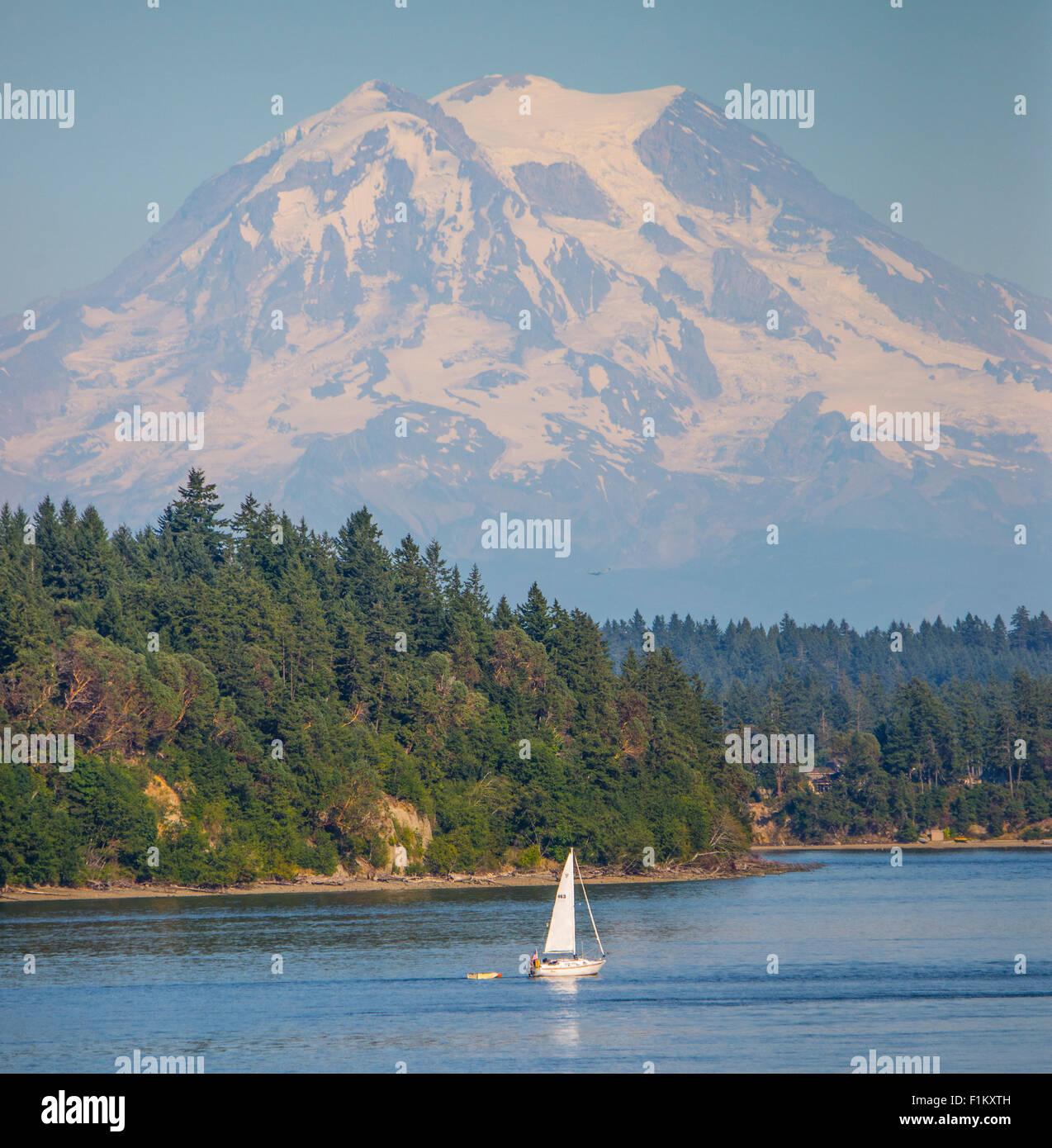 Landschaftlich reizvolle Nahaufnahme des Mount Rainier mit Menschen, die ein Segelboot segeln. Puget Sound, Squaxin Stockfoto