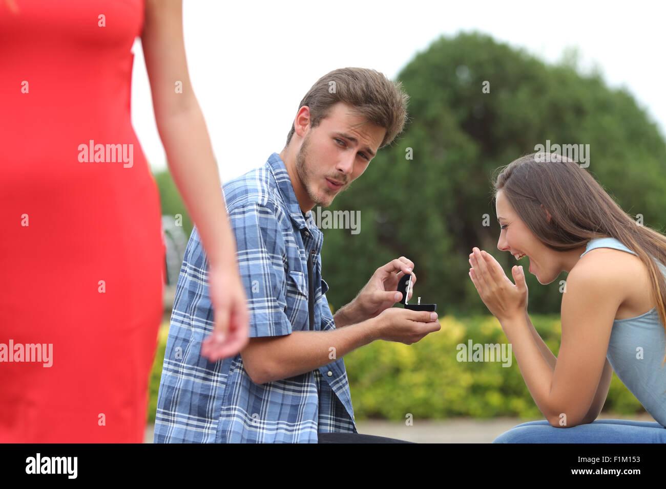 Betrüger Mann betrug während einen Heiratsantrag mit seiner unschuldigen Freundin Stockfoto