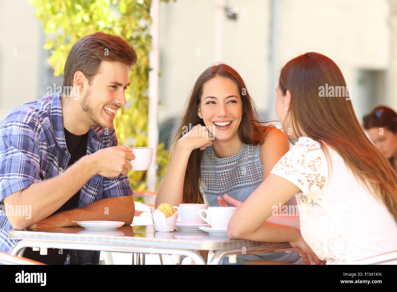 Drei glückliche Freunde reden und Lachen in einer Café-Terrasse Stockbild