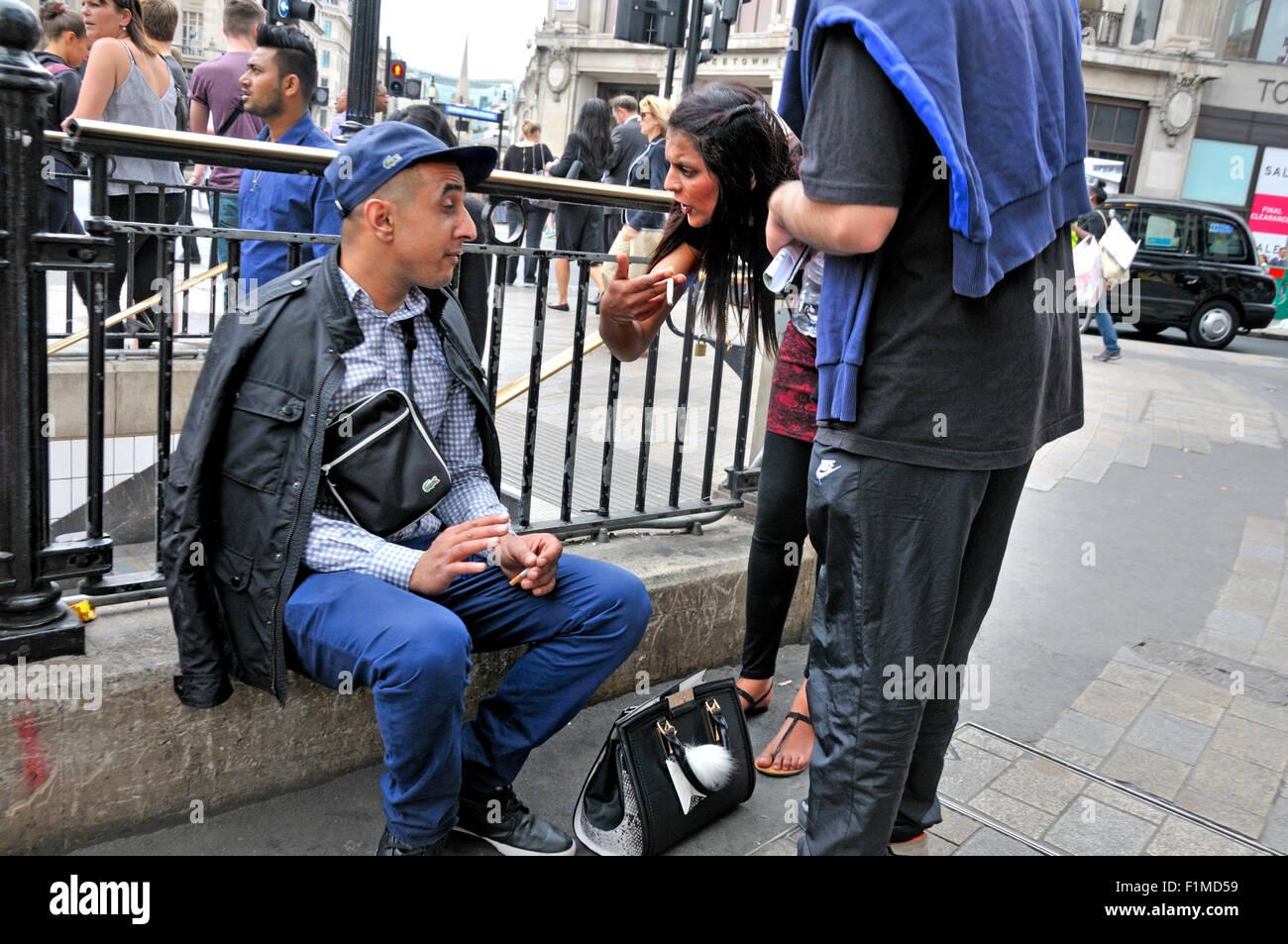 London, England, Vereinigtes Königreich. Menschen, die eine angeregte Diskussion in Oxford Circus Stockbild