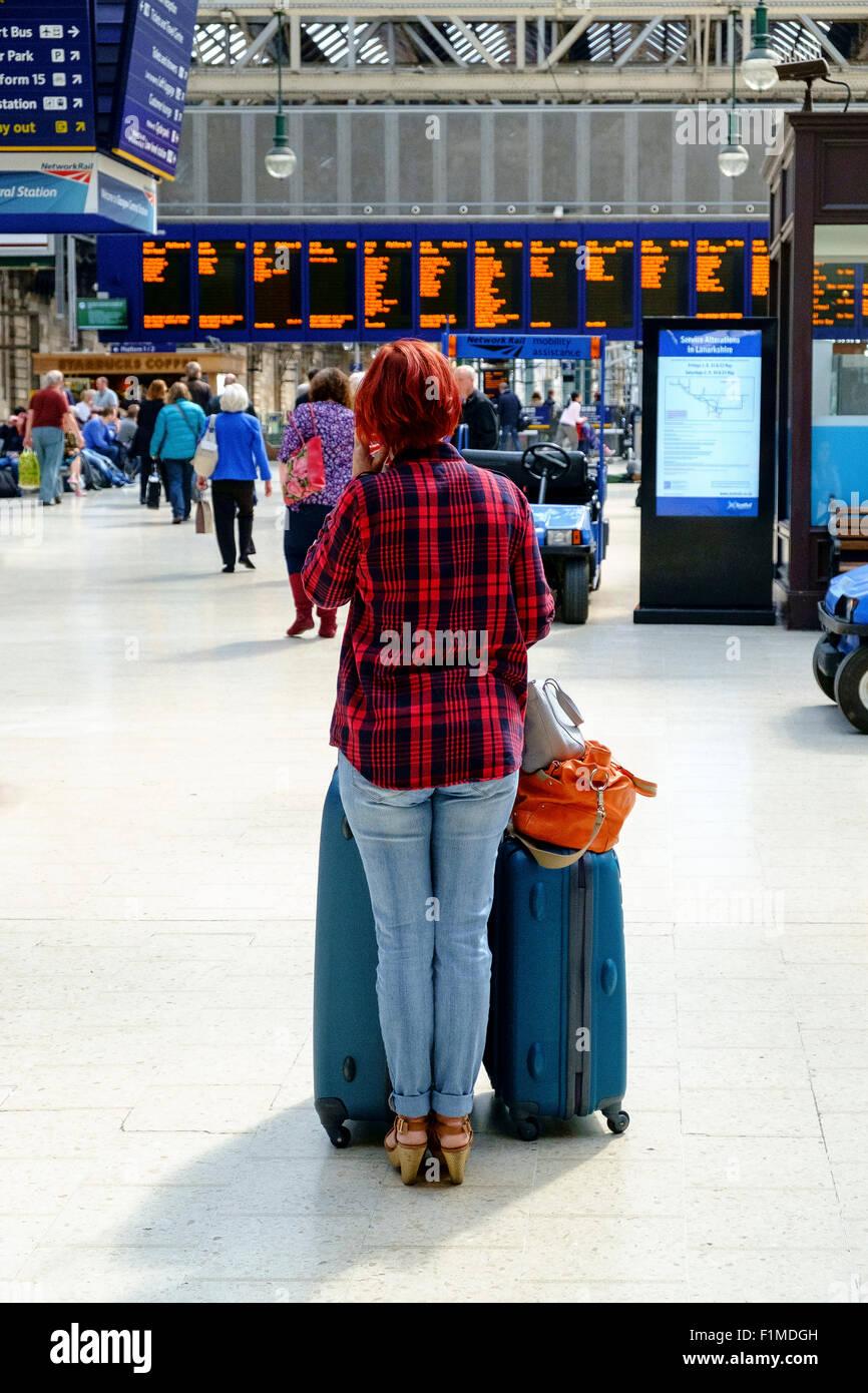 Frau wartet Zug Bahnhof Gepäck Gepäck uk Stockbild