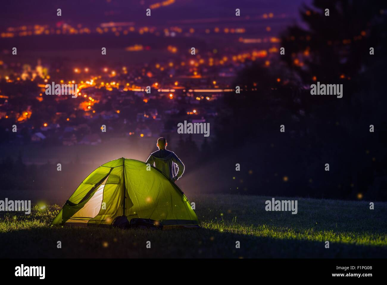 Natur Camping mit Scenic City Blick hinunter ins Tal. Stadtbild bei Nacht und den Camper mit beleuchteten Zelt beleuchtet. Stockbild