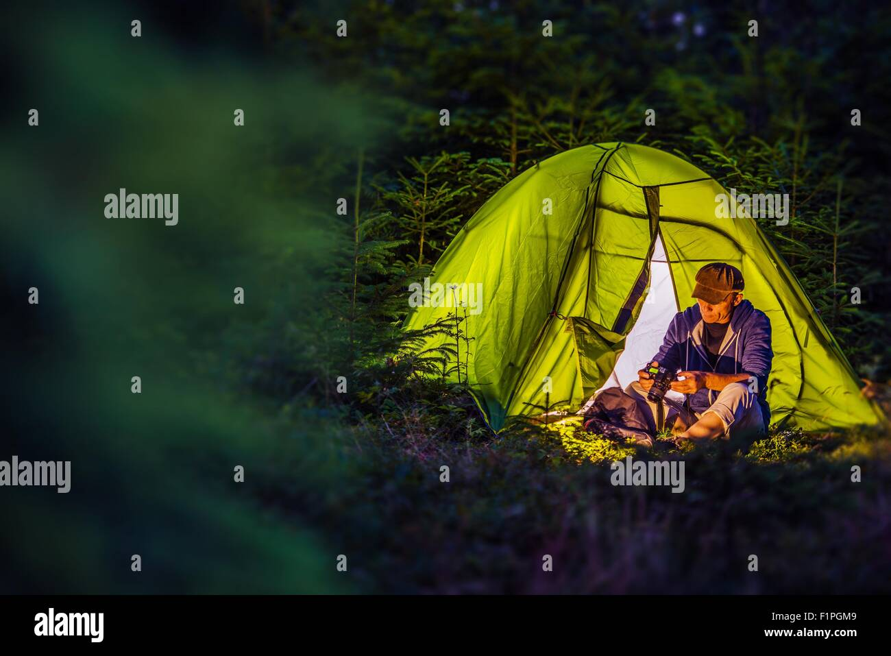 Übernachtung-Wald Camping. Mittleren Alters kaukasische Wanderer mit seiner digitalen Kamera und die beleuchteten Stockbild