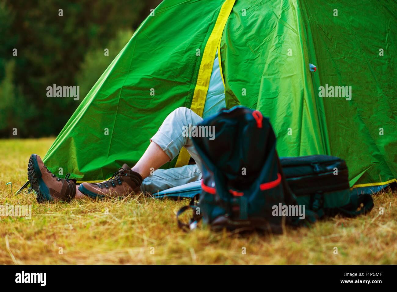 Ruhende Wanderer in seinem Zelt von mittlerer Größe. Wilden Campingplatz. Wandern und Zelten Thema. Stockbild