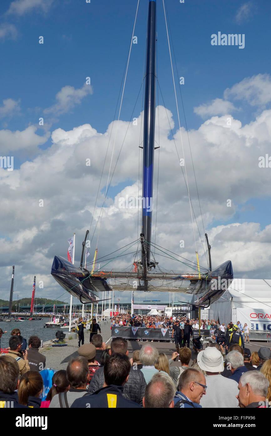 Menschen sammeln und nutzen Sie die Gelegenheit zu sehen, Swedish America Cup 72 Klasse Katamaran von unten, wenn es für Flügel-Segel-R aufgehoben wird Stockfoto