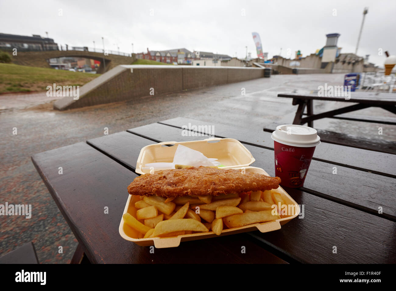 frittierte billige Fish & Chips an einem nassen Sommertag an einem Badeort in Nord Wales uk Stockbild