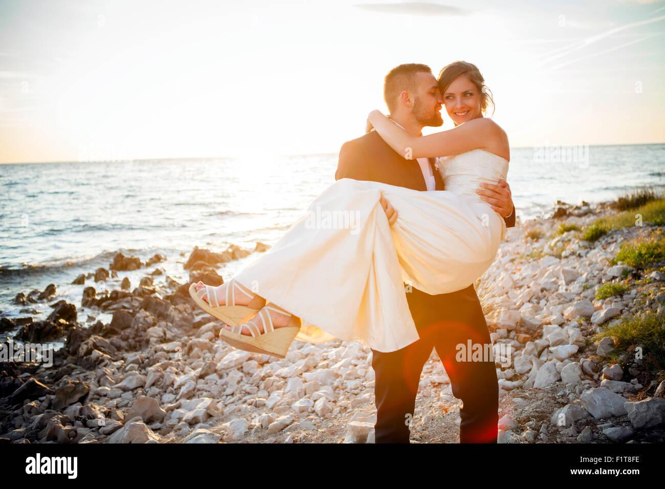 Bräutigam trägt Braut am Kiesstrand bei Sonnenuntergang Stockbild