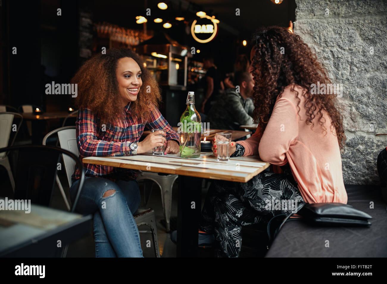 Zwei junge Frauen reden, sitzen in einem Restaurant. Afrikanische Frau lächelnd und Chat mit ihrer Freundin Stockbild