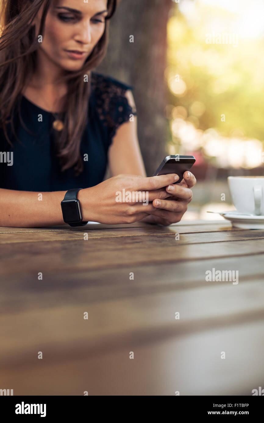 Bild der jungen weiblichen lesen eine SMS-Nachricht auf ihr Smartphone zugeschnitten. Frau mit Smartphone in ein Stockbild