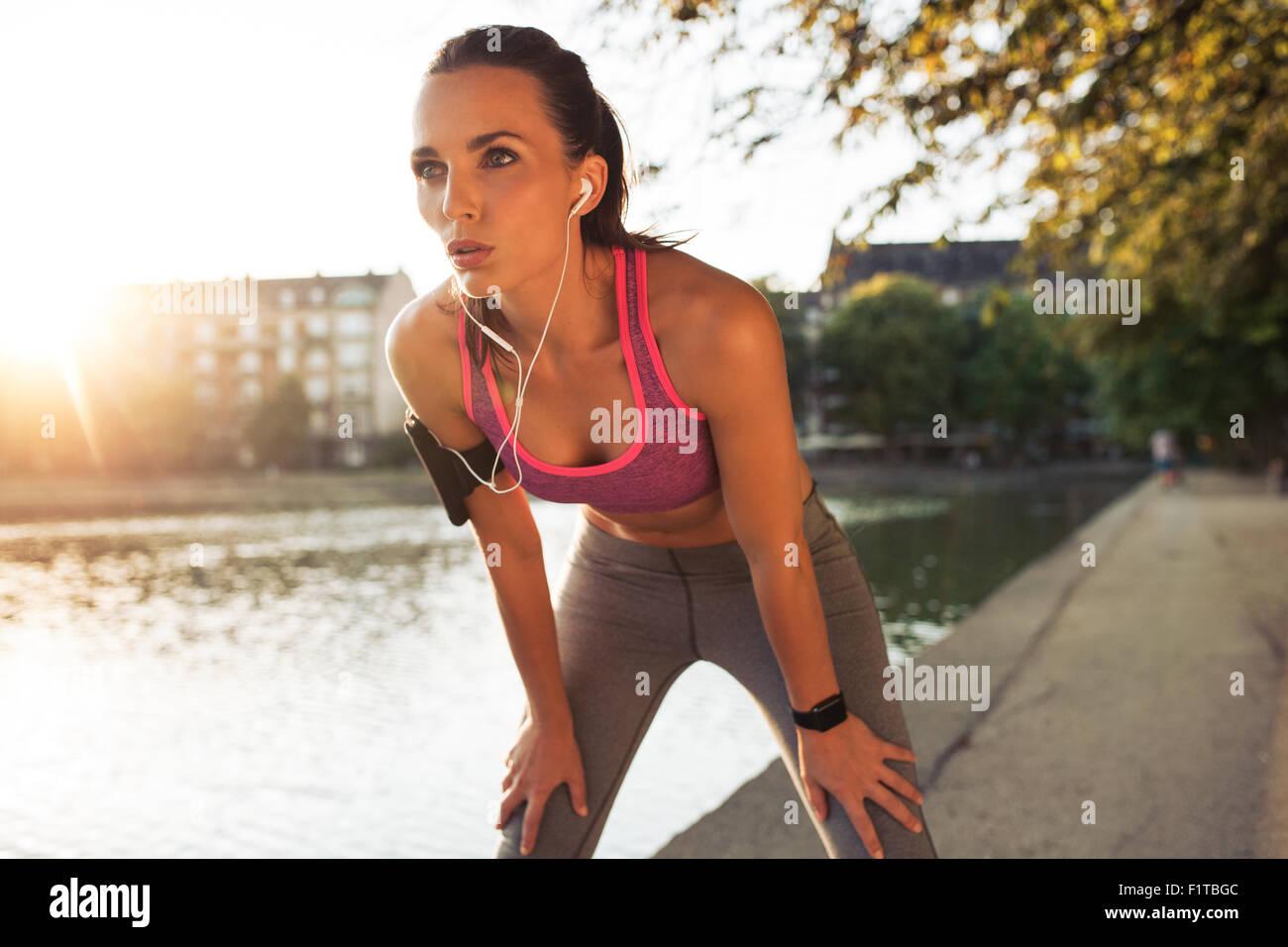Weibliche Läufer stehend gebeugt und fangen ihr Atem nach einer laufenden Sitzung entlang See in der Stadt. Stockbild