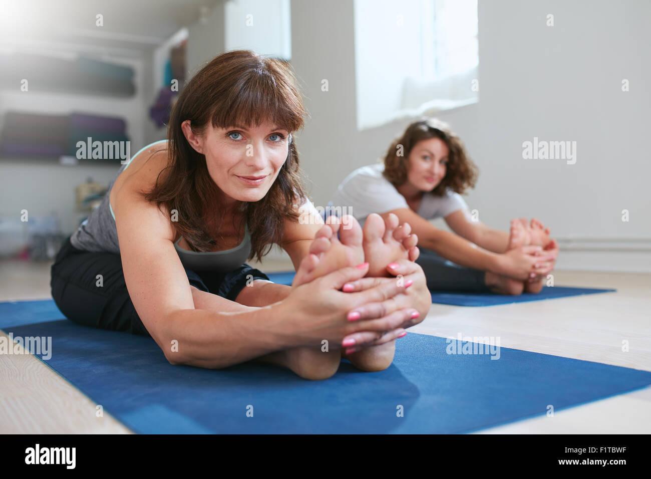 Frauen, die zusammen im Fitness-Studio, Yoga üben Paschimottanasana darstellen. Fitness Frauen sitzen nach vorne Stockfoto