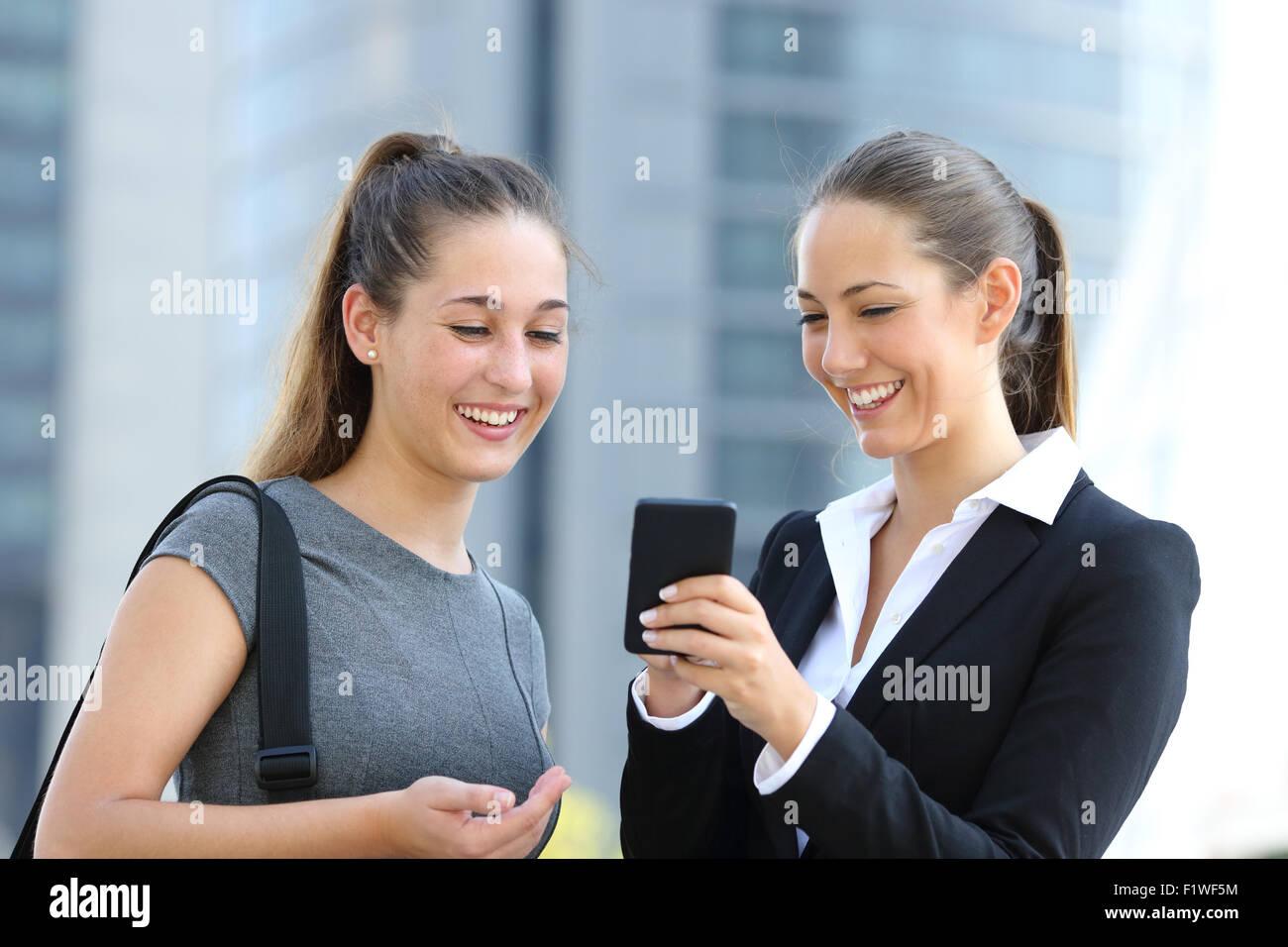 Zwei Unternehmerinnen sprechen über Smartphone auf der Straße mit Bürogebäude im Hintergrund Stockfoto