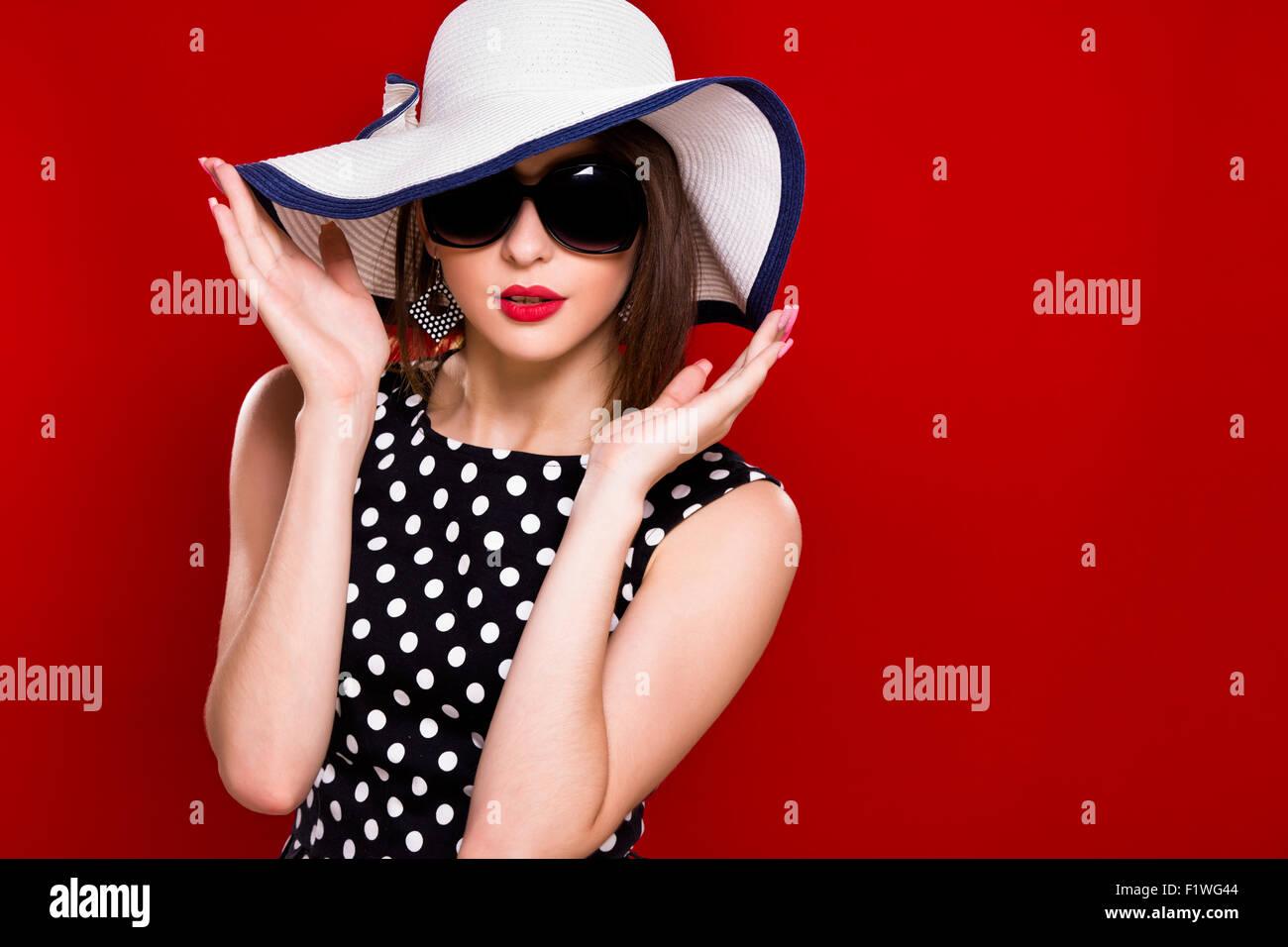 Hübsches junges Mädchen mit dunklen Haaren, in schwarz mit weißen Punkten  Bluse, Sonnenbrillen und weißen Hut tragen posiert auf einem roten Hinterg 230cd3e6dc