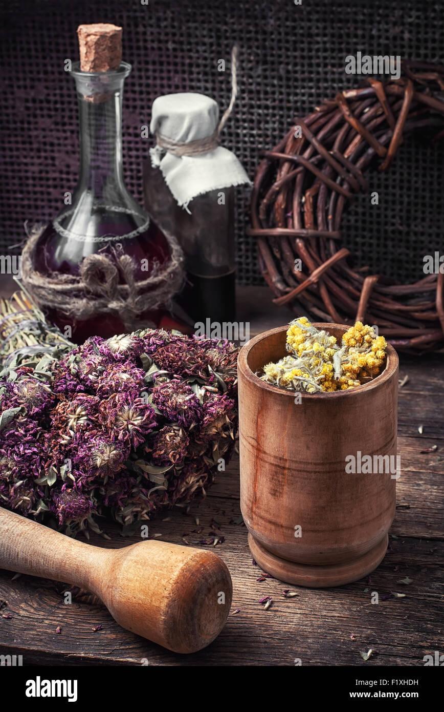 Schneiden Sie Haufen Heilpflanzen, Mörtel auf Holztisch. Abgeschwächt. Stockbild