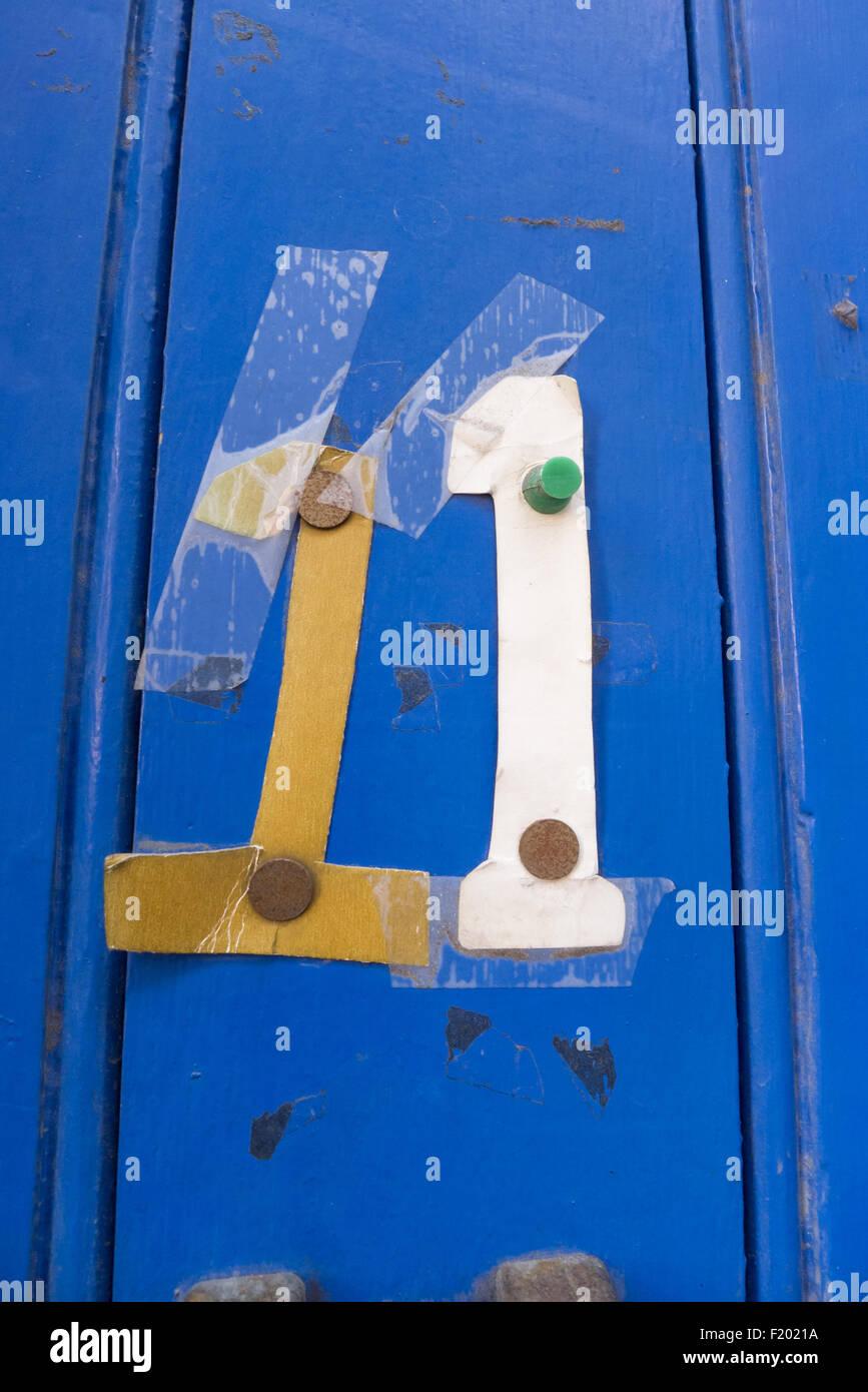 Spitalfields, London. Fixiert und mit Klebeband Pappe Zahlen Nummer elf 11 blau bemalte getäfelte Tür. Stockbild