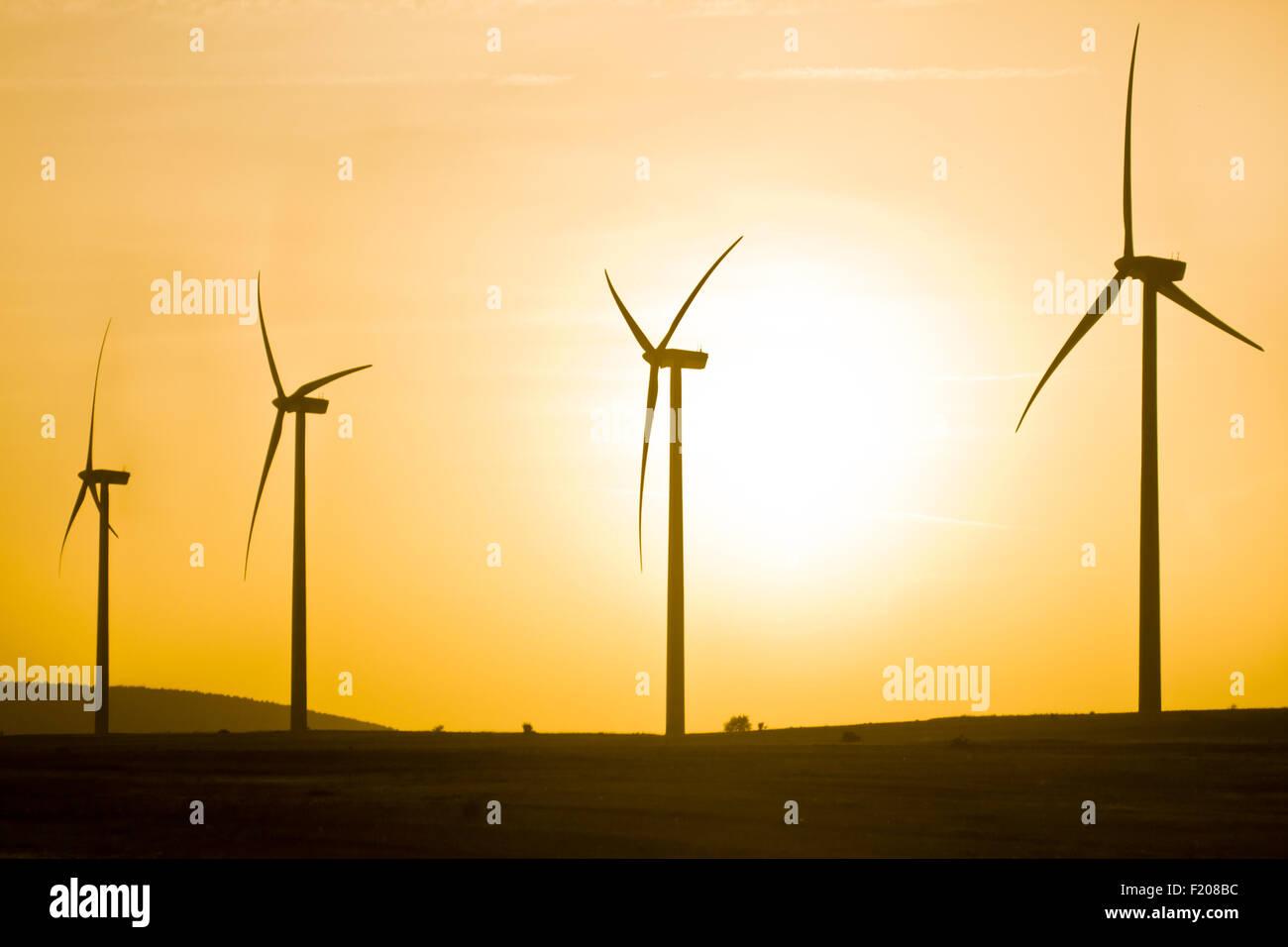 Windenergieanlagen bei Sonnenuntergang Stockbild