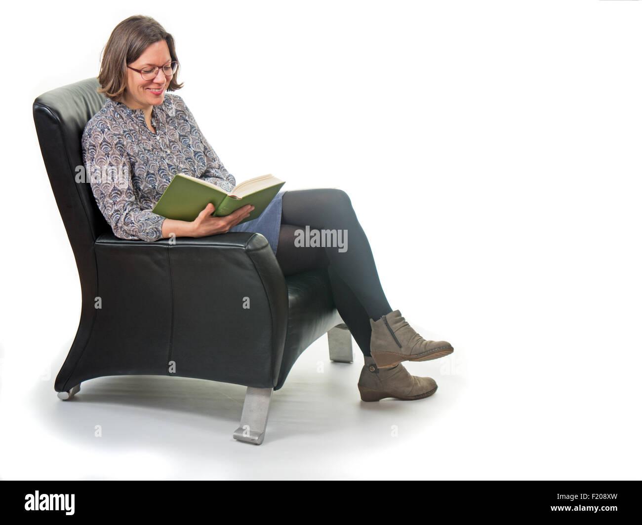 Lesende Frau im Sessel Stockbild