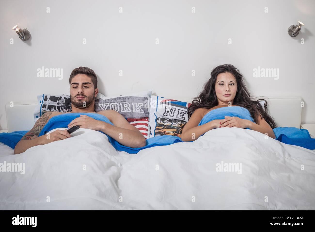 Junges Paar liegend im Bett zu schmollen Stockbild