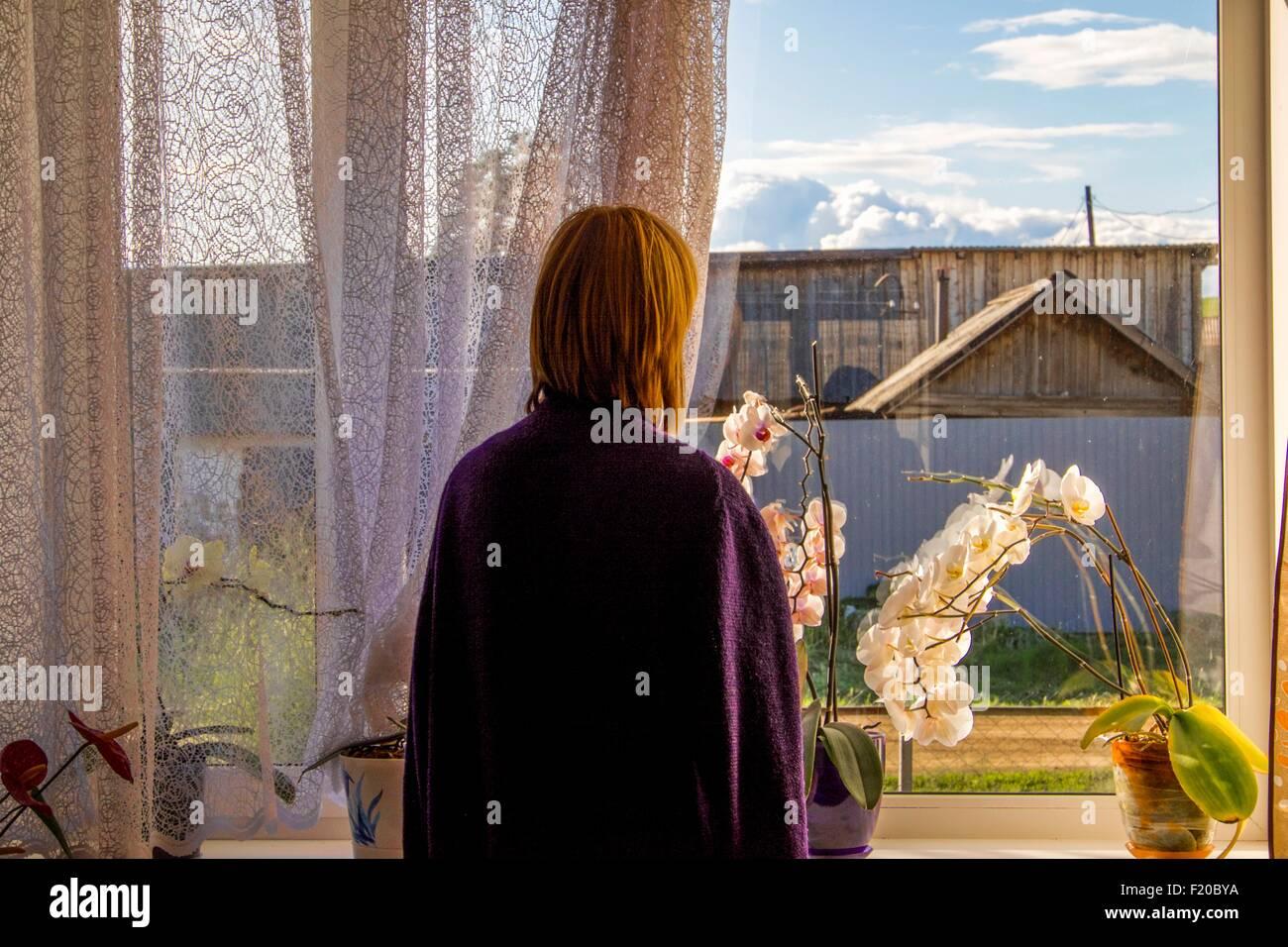 Frau mit Blick auf landwirtschaftliche Gebäude aus dem Wohnzimmerfenster Stockbild
