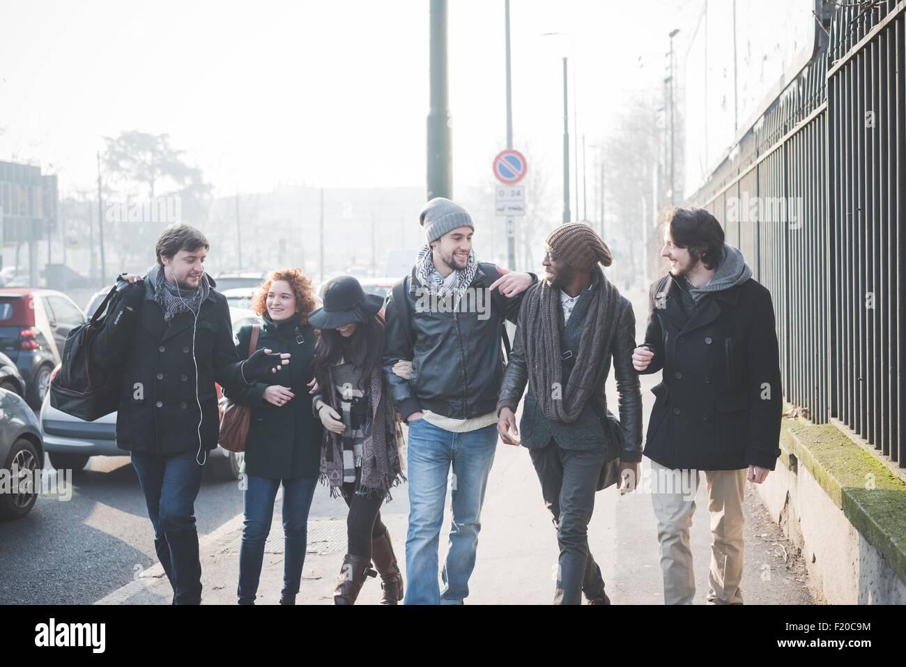 Sechs junge Erwachsene Freunde im Chat beim Spaziergang entlang der Stadtstraße Stockfoto