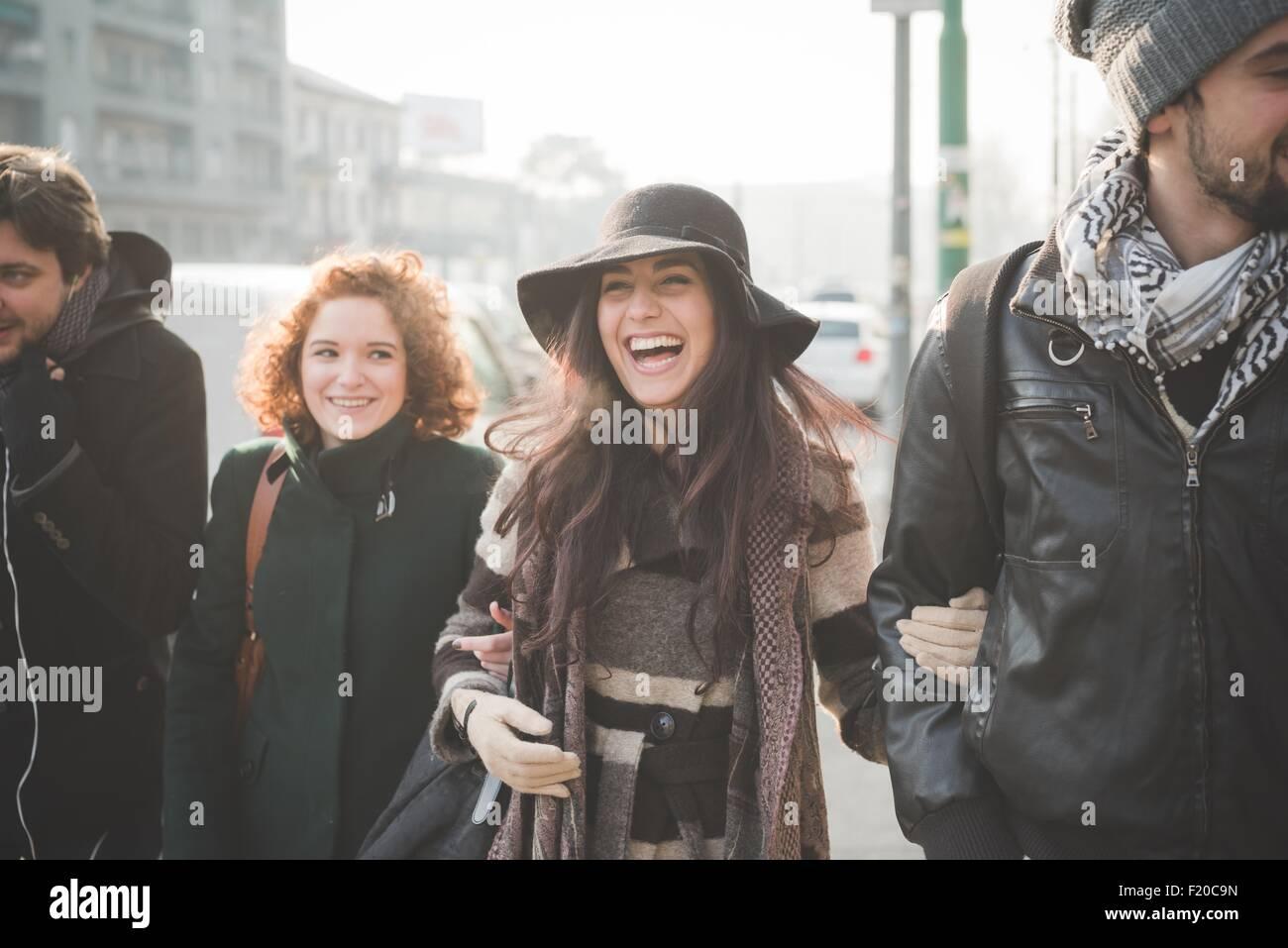 Vier junge Erwachsene Freunde schlendern arm in Arm entlang Stadtstraße Stockfoto