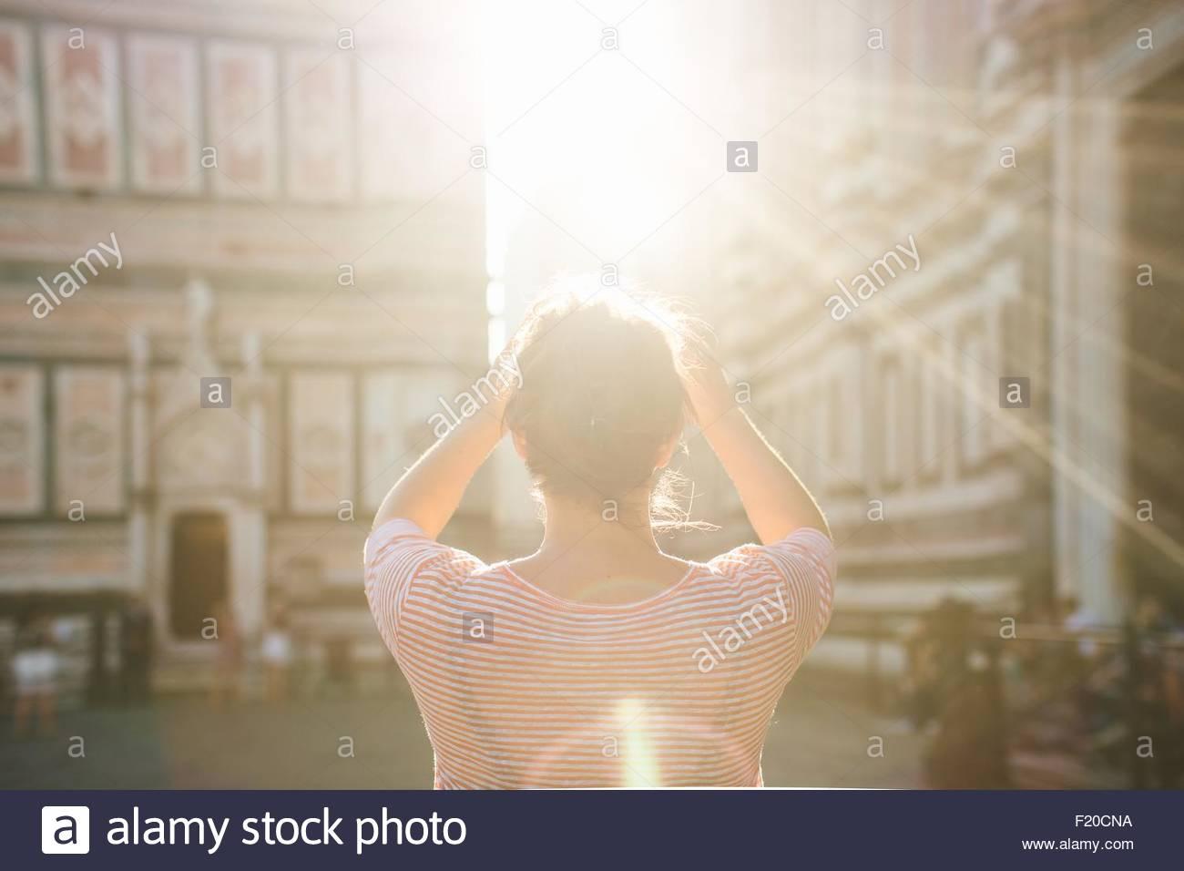 Rückansicht der Mitte Erwachsene Frau, erhobenen Armen, lens Flare, Dom, Florenz, Italien Stockbild