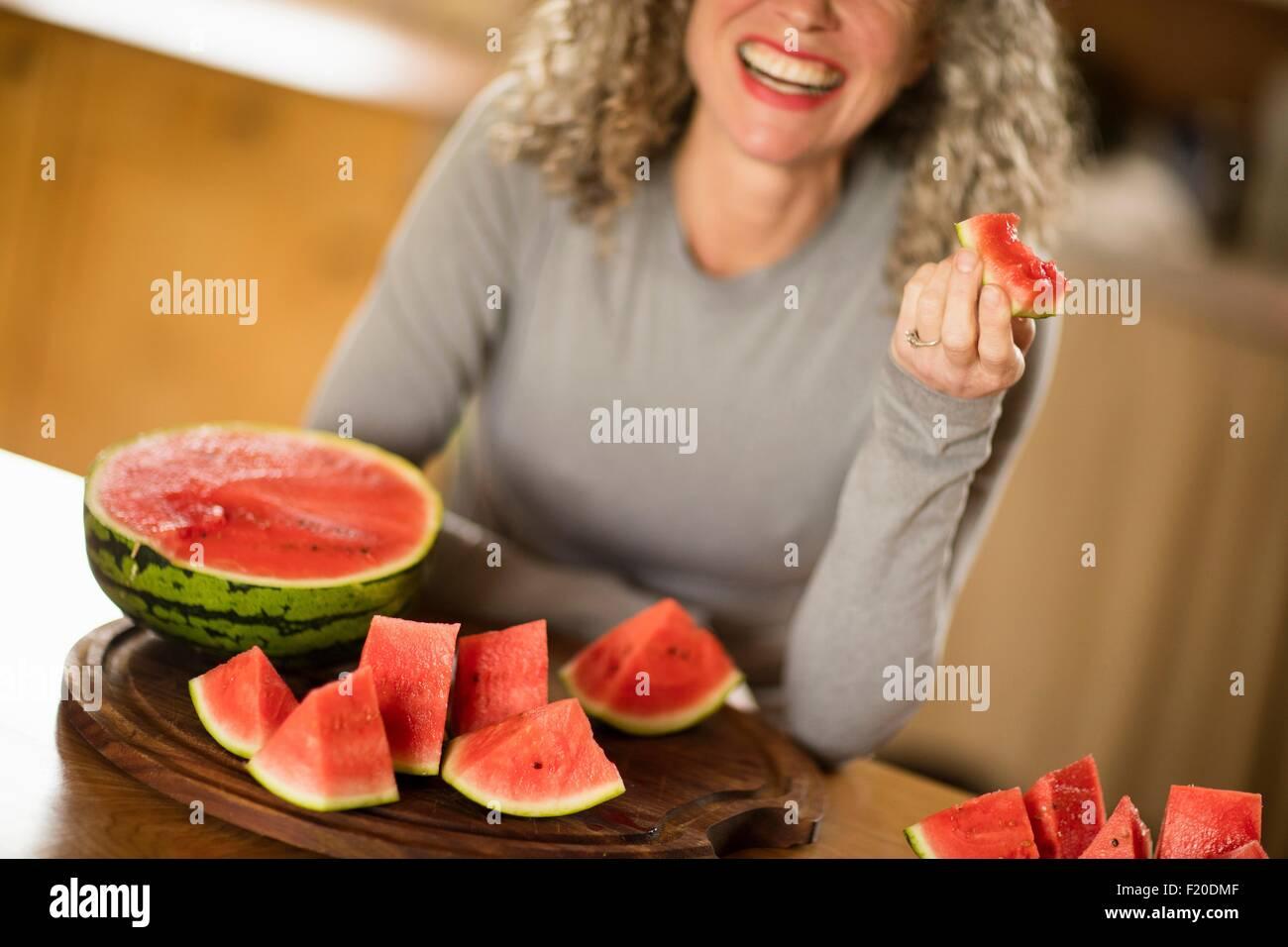 Reife Frau Essen Wassermelone in Küche Stockbild