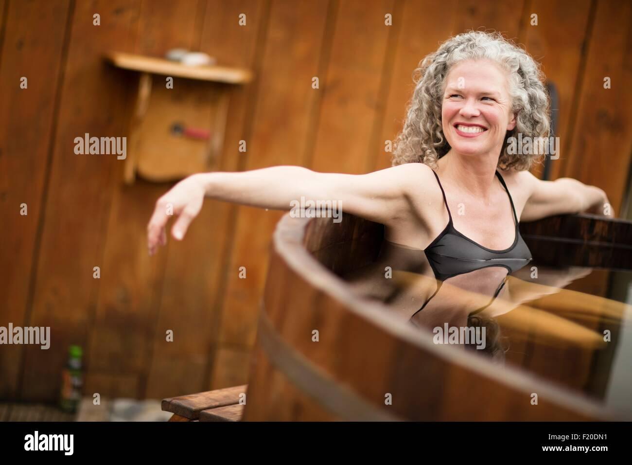 Reife Frau im Whirlpool bei Eco Retreat lächelnd Stockbild